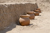 Clay pots are lined up in front of a wall on top of the clay pyramid of Huaca Pucllana, Lima, Miraflores, Peru