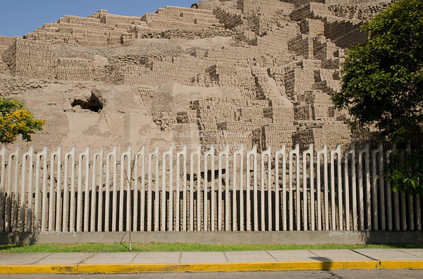 An ordinary fence separates the ancient adobe pyramid of Huaca Pucllana, a ceremonial and administrative center for the Lima Culture (200 AD - 700 AD), from the residential streets of Miraflores, Lima, Peru