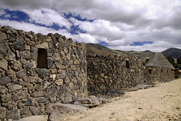 Raqchi 5206<br /> Qolcas were long term storage houses for foods in the event of conflicts or shortages in the Inca Empire. Constructed with volcanic rock in a circular form with the base a little over 30 feet and almost 10 feet high with a conical thatched roof. Raqchi had  160 Qolcas in the complex.