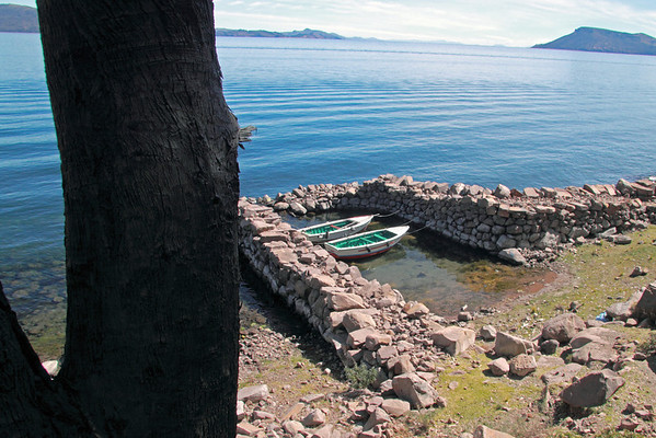 Titicaca 5341<br /> A couple of small boats in a protective harbor at Port Alsuno on the island of Taquile on Lake Titicaca.