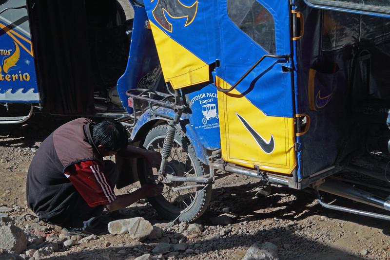 Ollantambo 4219<br /> Cab driver working on his three wheel motor bike used as cabs in Ollantambo.