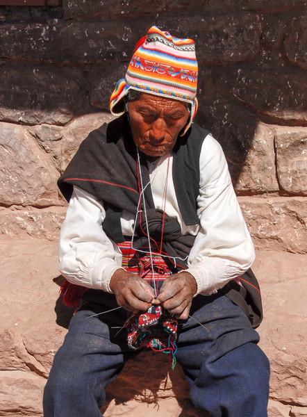 Local Peruvian man knitting - Lake Titicaca, Peru