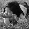 Pensive girl rests in grass Peru