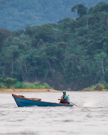 A local rides a boat down the Madre de Dios River
