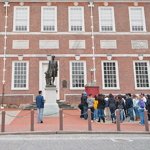 Tourists visiting Independence Hall and George Washington Statue in Philadelphia.