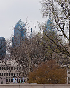 From left to right: Two Liberty Place, William Penn statue on top of Philadelphia City Hall, and One Liberty Place (all behind trees).  View from Franklin Square Park.