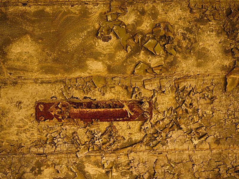 Rusted handle on decaying door
