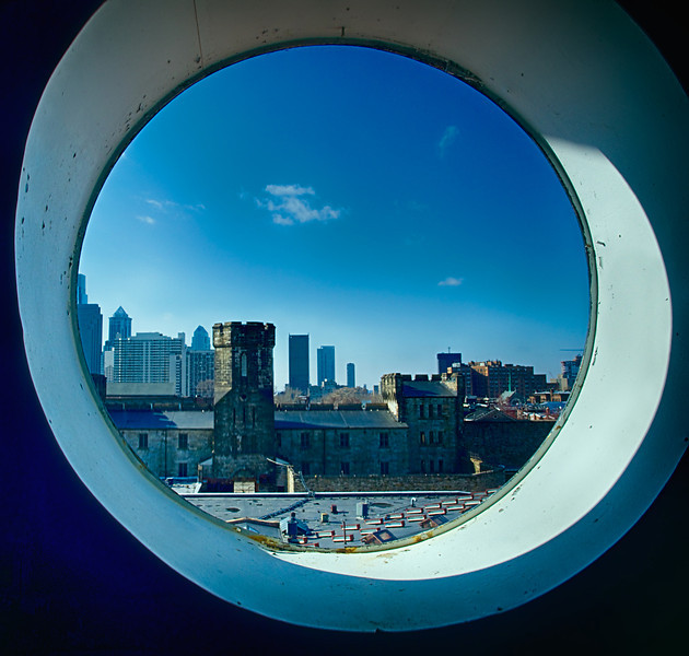 View of city from round window on stairway to tower.