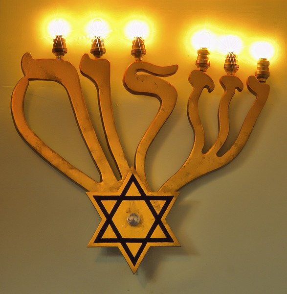 The  candelabra's arms spell Shalom, or peace, in Hebrew and are supported by the Star of David.