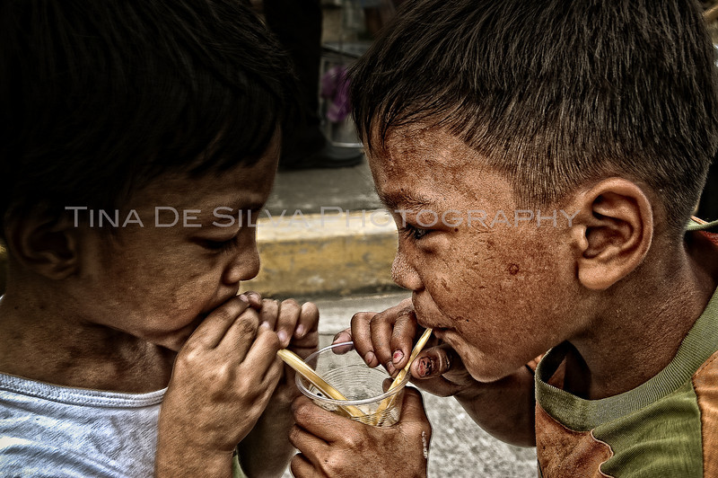Street Children<br /> A street child shares a native refreshment with one of his peers.<br /> Intramuros, Manila<br /> Philippines