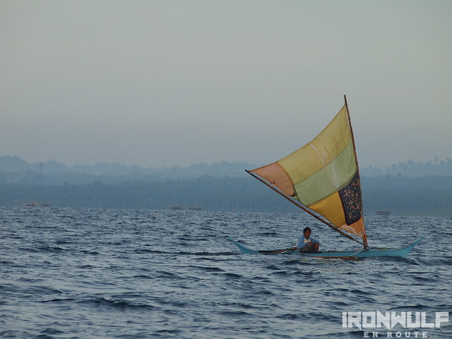 Lone boat with colorful sail