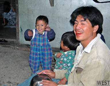 Father on tin pan drums, sons dancing.  The red mouth is from chewing beetle nuts.