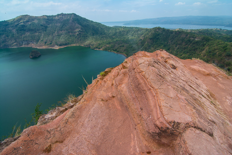 Red sandstone (yes, it's sedimentary!) on the crater rim looking down in the crater lake of the volcano in Lake Taal, March 2014. You can just see some steam blowing out from a hole at the top of the red rock.