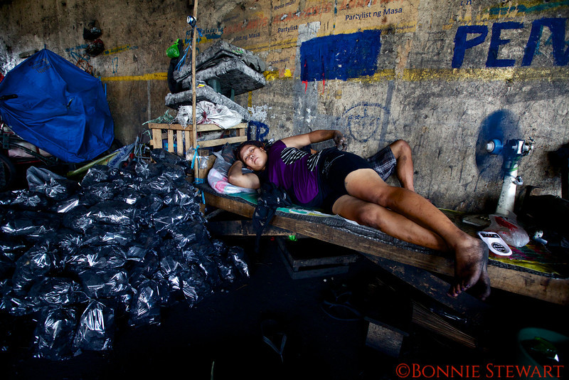 Coal packer and resident of the Santa Mesa community of homeless living next to the train tracks below an underpass in Manila