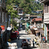 """Back in Banaue. Down in the street, one of the hundreds of tricycles that create 95% of Banaues traffic.<br /> It seems to be a habit to buid """"half-finihsed"""" houses... or at least to always leave the steel peeking out the concrete so you can easily extend your house? who knows."""