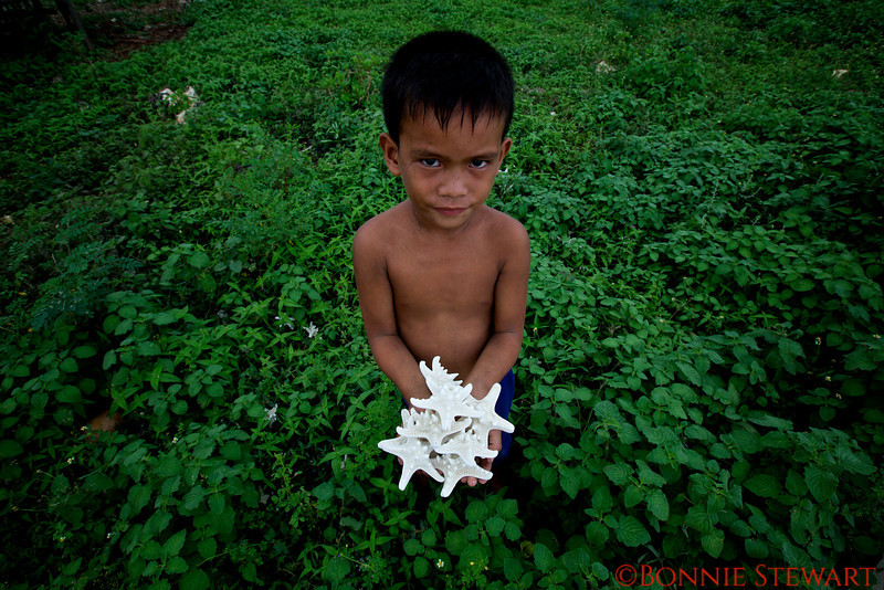Village child with star fish from a village in Cebu that farms starfish, sea urchins and sand dollars for export