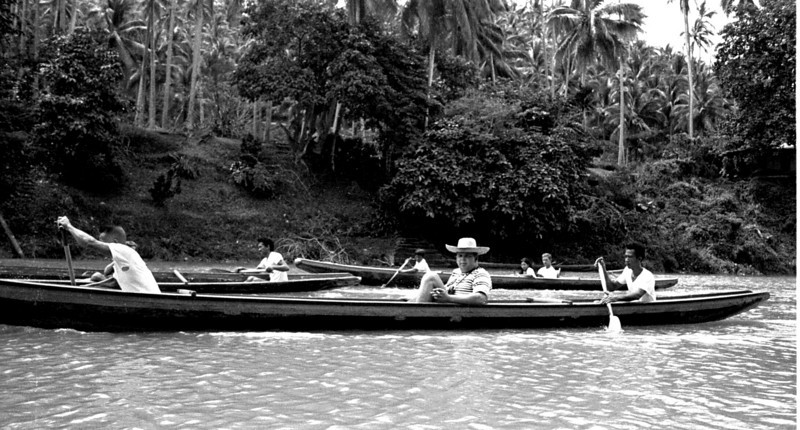 "Richard Cope, built to play halfback, takes to the river like a great white hunter. His straw bent to the wind. He doesn't know it yet but his canoe team is about to make a bad move in an upcoming rapid that will propel him into the Pagsajan. He'll roll on the bottom well over the big man's head. He'll clutch his camera but loose his hat. It will float past me, I'll grab and miss. He'll break to the surface with a child-like smile, and the paddle men will fret over his camera. He'll smile, hold up the underwater camera and say, ""Nikonos, Nikonos, no problem, it's made for the water."""
