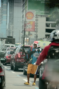 Street vendor wading through the bumper-to-bumper traffic outside of Manila.