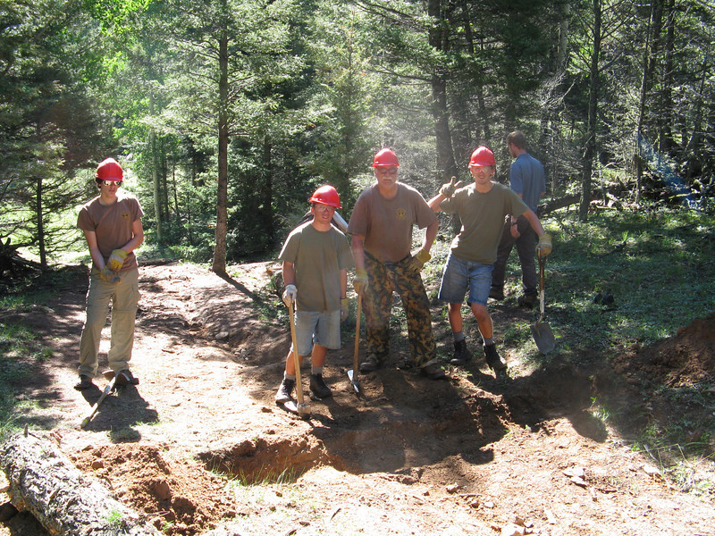 Digging trenches for logs to close off an old unused trail. The logs help prevent erosion.
