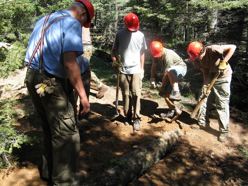 Burying the log across the trail.