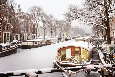 Canal boats, terrace houses and deciduous trees around a frozen canal in Amsterdam.