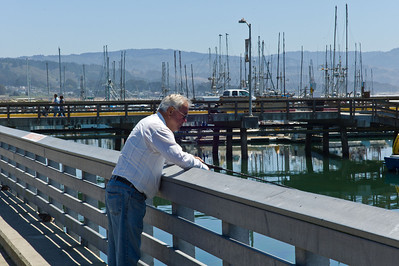 Older gentleman enjoying dropping a line in the calm waters of the harbor.
