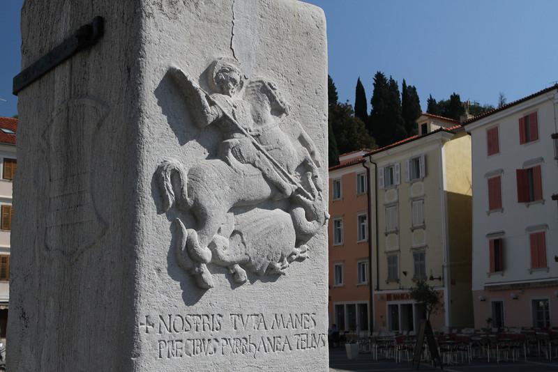 Back at Tartini Square (Tartinijev trg) note that the town's 15th century flag poles at the entrance bear Latin inscriptions praising Piran.  This one, to the Left, shows St. George, the patron (the town's Coat of Arms).