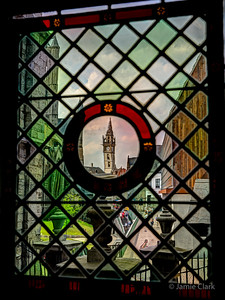 Clock tower through stained glass. Ghent, Belgium