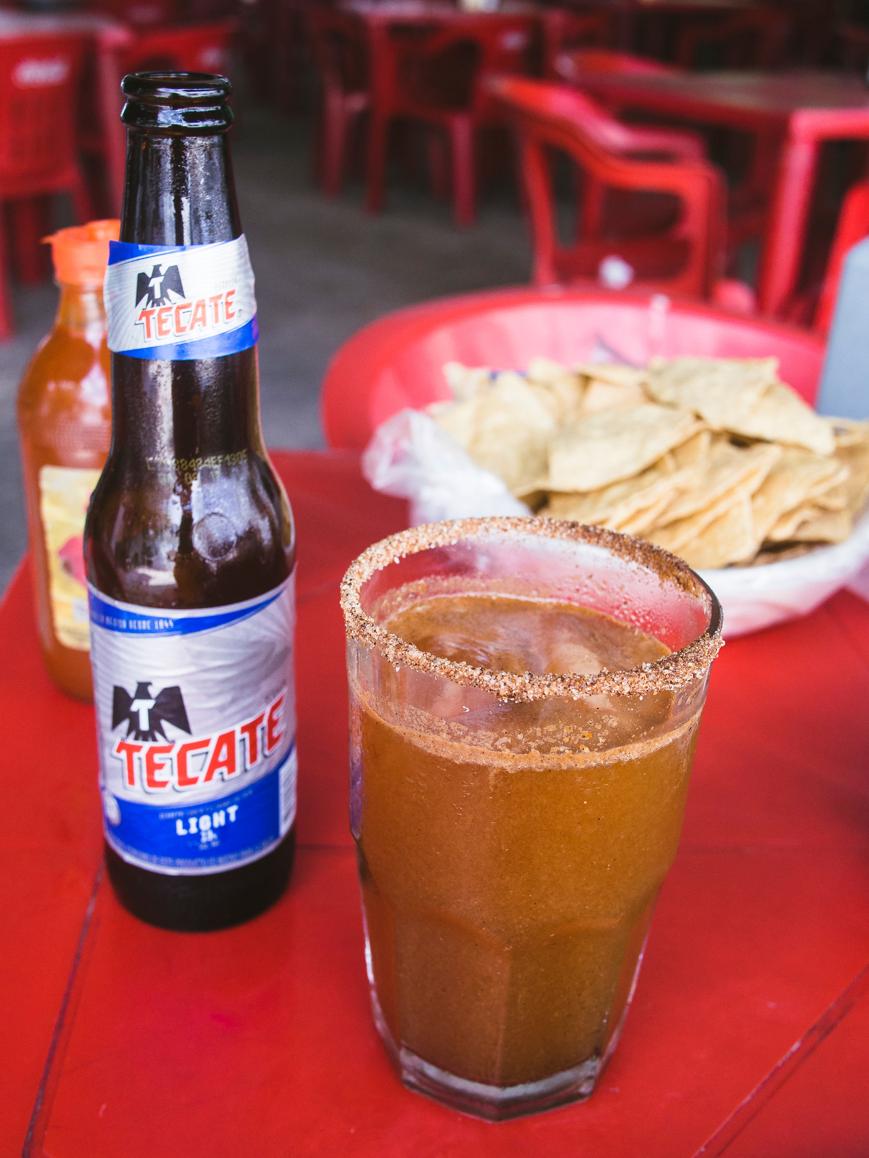 Michelada beer cocktail from Mexico with bottle of Mexican beer beside it and tortilla chips in the background.