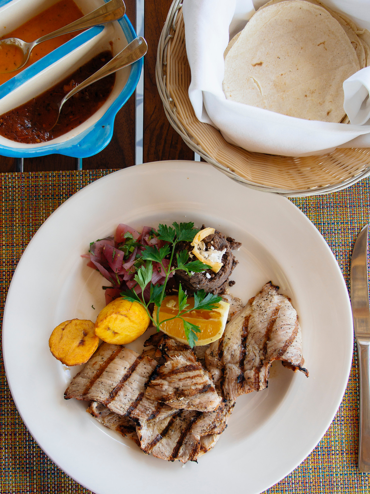 Poc chuc in Mexico is Mayan grilled pork that is marinated in sour orange juice and served with pickled onions.