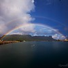 A double rainbow stretches across the harbor.
