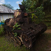 An abandoned Japanese tank gathers rust off the main thoroughfare in Kolonia.
