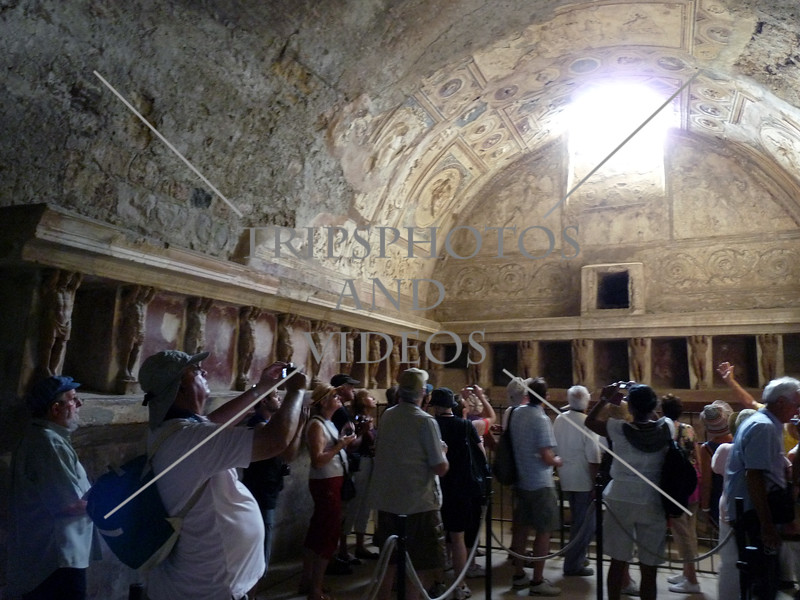 A group of visitors touring inside a bath house at the Pompeii ruins in Italy.