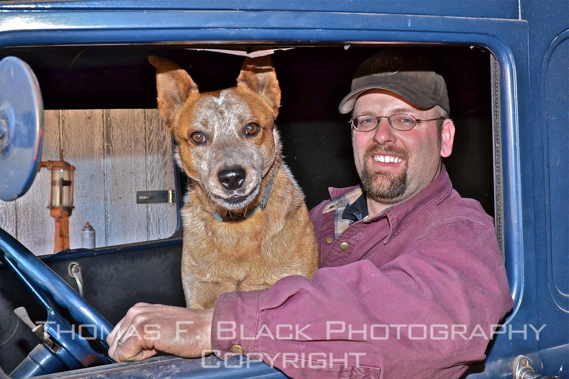 Jeff Parady and one of his dogs pose inside cab of restored 1930 Ford delivery van inside his repair shop. [UFP011212]