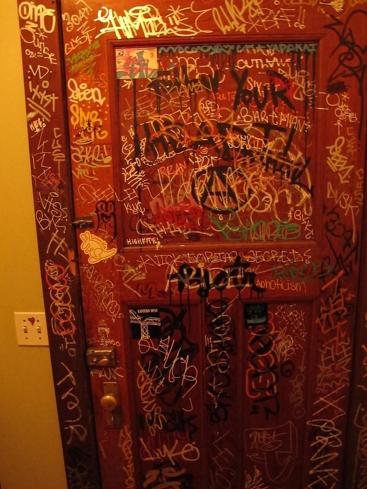 Coffeeshop bathroom door graffiti.