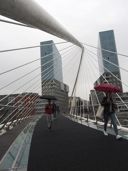 Rainy day on the Zubizuri pedestrian bridge in Bilbao, Spain.