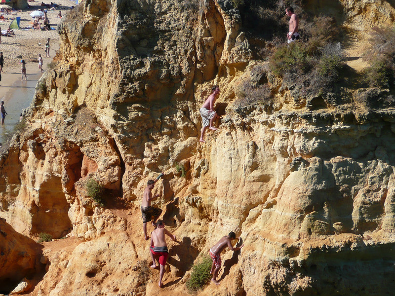 Kids climbing the rocks and diving into the water.