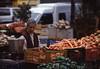 018  Viana do Costello, Praça da Maria II, vrouw met wortels op groente- en fruitmarkt