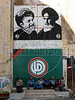 Men sit below a wall painting of Assasinated Lebanese religious leader Moussa Al-Sadel, top left, Iranian leader Ayatollah Khomeni and the Hezbollah party banner, below, in Beirut, Lebanon. The Hezbollah, known internationally as a terrorist group, also is a legitimate political party in Lebanon, with eight members of parliament.<br /> (Australfoto/Douglas Engle)