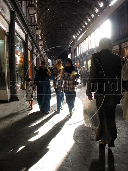 Pedestrians walk through the covered souq, or market, of the old city in Damascus, capital of Syria. Almost anything can be bought at the souq, a traditional part of Middle Eastern cities.(Australfoto/Douglas Engle)