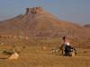 A man walks with a bicycle past the 17th century Arab castle Qala'at ibn Maan in Palmyra, in the Syrian Desert.(Australfoto/Douglas Engle)