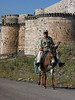 A man rides a donkey past the outer wall of the 12th century Krak des Chevaliers castle, situated on a mountaintop in the Homs Gap, the only and strategic break in the coastal mountain range between Turkey and Lebanon. In its almost 200 years under Christian Crusader knights, the formidable double-walled castle was never breached by attacking Arabs.(Australfoto/Douglas Engle)