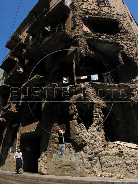 A man walks past a war-damaged building in Beirut. scars of the 1975-1992 Lebanon Civil war can still be seen as rebuiding continues at a feverish pace.(Australfoto/Douglas Engle)