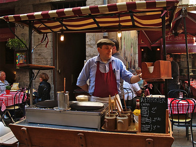A Frenchman makes crepes at a street bistro. Lyon, France.