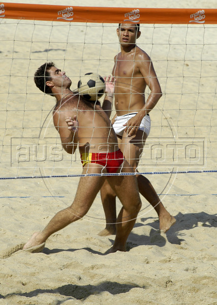 "Beach goers plays ""foot-volley,"" a uniquely Brazilian sport which combines soccer skills with a volleyball court, on a beach of Rio de Janeiro. (AustralFoto/Douglas Engle)"