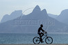 "A cyclist rides past the ""Two Brothers"" mountain on the Ipanema beach of Rio de Janeiro. (AustralFoto/Douglas Engle)"