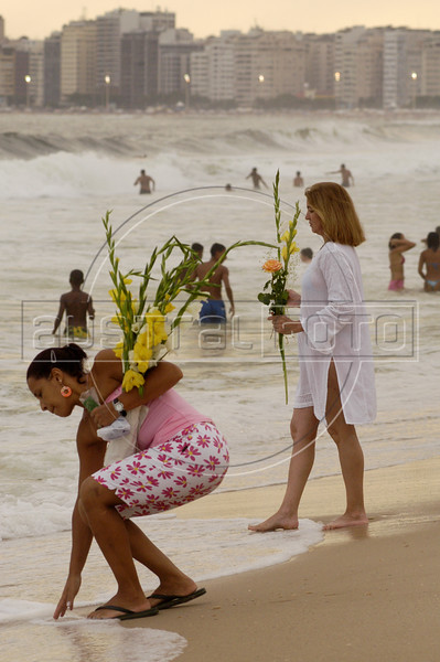 Brazilians give offerings of flowers to the ocean on Copacabana Beach as they pray to sea goddess Yemanja, the Yoruba goddess of the sea in an afro-Brazilian new year's tradition in Rio de Janeiro, Dec. 31, 2004.(AustralFoto/Douglas Engle)