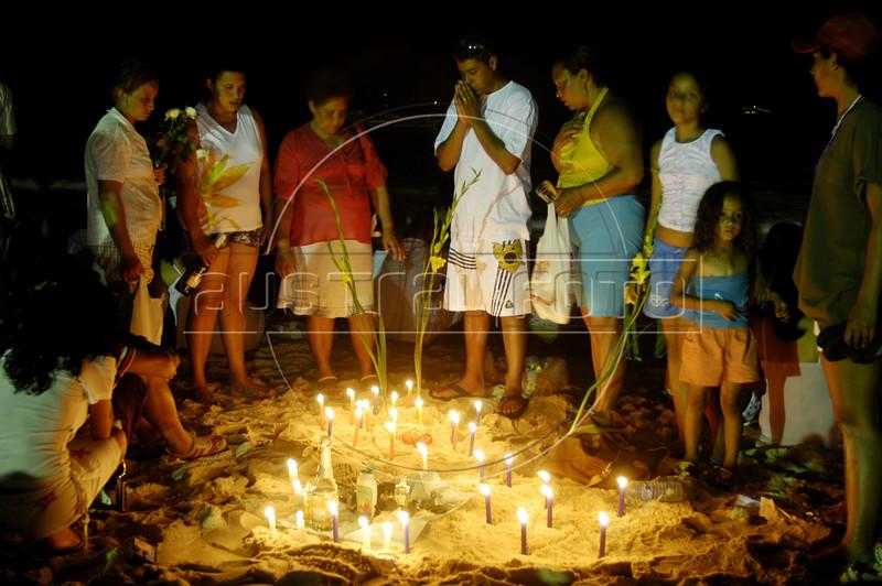 Brazilians stand around candles on Copacabana Beach as they pray to sea goddess Yemanja, the Yoruba goddess of the sea in an afro-Brazilian new year's tradition in Rio de Janeiro, Dec. 31, 2004.(AustralFoto/Douglas Engle)