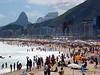 Beachgoers enjoy the summer sun on Copacabana beach in Rio de Janeiro. The Dois Irmaos mountain is at left, and the Pedra da Gavea mountain center.(AustralFoto/Douglas Engle)