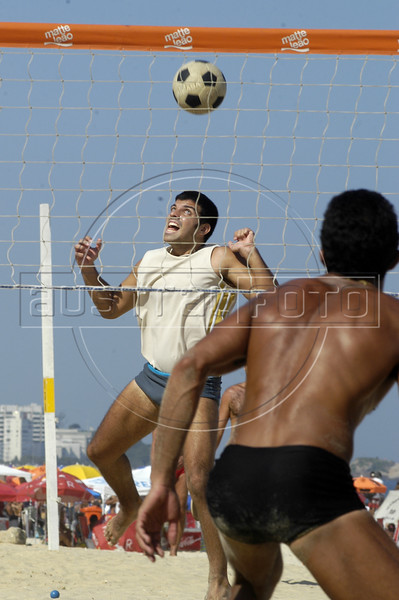 """Beach goers plays """"foot-volley,"""" a uniquely Brazilian sport which combines soccer skills with a volleyball court, on a beach of Rio de Janeiro. (AustralFoto/Douglas Engle)"""